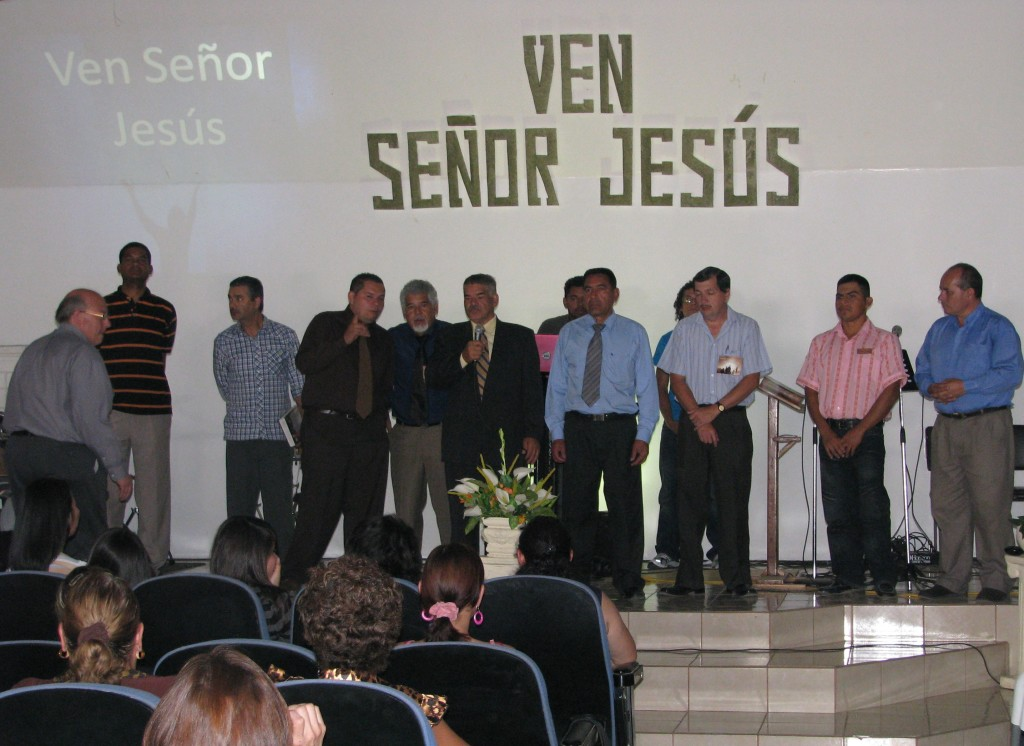 CR pastors being honored at 2012 Costa Rica For Christ national convention. On the left, Terry Hull comes to the stage to pray for these faithful brothers.